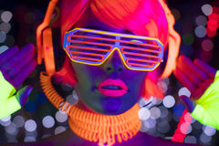 Glow uv neon disco female cyber doll robot electronic toy. Fantastic video of cyber raver woman filmed in fluorescent clothing under UV black light royalty free stock photo