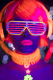 Glow uv neon disco female cyber doll robot electronic toy. Fantastic video of cyber raver woman filmed in fluorescent clothing under UV black light stock image