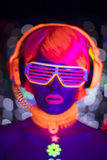 Glow uv neon disco female cyber doll robot electronic toy. Fantastic video of cyber raver woman filmed in fluorescent clothing under UV black light royalty free stock photography