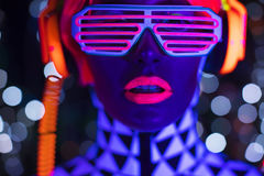 Glow uv neon disco female cyber doll robot electronic toy. Fantastic video of cyber raver woman filmed in fluorescent clothing under UV black light stock photo