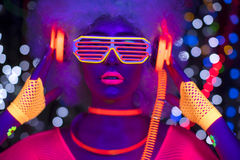 Glow uv neon disco female cyber doll robot electronic toy. Fantastic video of cyber raver woman filmed in fluorescent clothing under UV black light royalty free stock photos