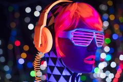 Glow uv neon disco female cyber doll robot electronic toy. Fantastic video of cyber raver woman filmed in fluorescent clothing under UV black light royalty free stock image