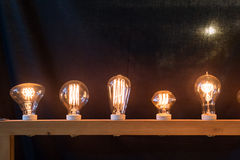Glow yellow design light bulbs in black Royalty Free Stock Photography