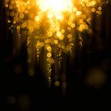 Glowing abstract gold background. Abstract background falling down out of focus lights Royalty Free Stock Photography
