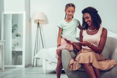 Glowing Afro-American mother looking at the drawing of daughter. Showing drawings to mom. Glowing charming smiling alluring dark-haired Afro-American mother royalty free stock photography