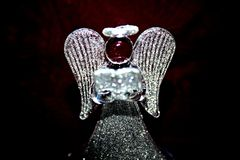 Glowing angel. Glowing glass angel on a background of satin fabric royalty free stock photography