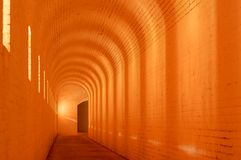 Glowing Arched Hallway. Aged passageway with arched glowing lights from windows Royalty Free Stock Image
