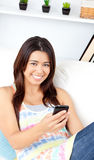 Glowing asian woman holding a cellphone smiling Royalty Free Stock Photos