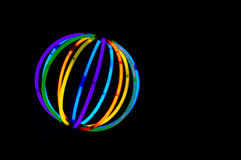 Glowing Ball. A multicolored glowing ball made from fluorescent glow sticks on black background Royalty Free Stock Photos
