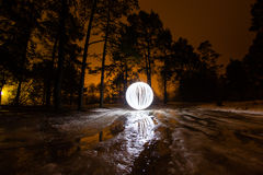 Glowing ball on the melting ice in the spring forest Stock Photos
