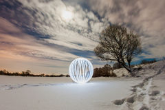 Glowing ball on the surface of a frozen lake Royalty Free Stock Photos
