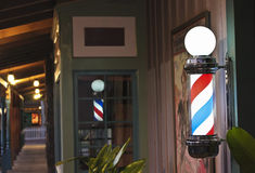 A Glowing Barber Pole on a Shop Porch. A Glowing Barber Pole on a Barbershop Porch at Night Stock Image