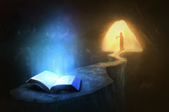 Glowing Bible in cave. Seeking a glowing Bible inside a cave royalty free stock image