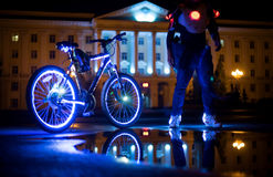 Glowing bicycle is reflected in the water. Nearby is a man in luminous shoes-2 Royalty Free Stock Images