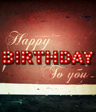 Glowing birthday greetings over distressed paint Stock Photo