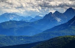 Glowing blue mist above forested ridges of Dolomites, Italy Royalty Free Stock Images