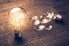 Glowing and Broken Light Bulb, Learning From Mistake. Glowing and broken light bulb comparison concept, problem and solution, failure and success, learning from Royalty Free Stock Photo