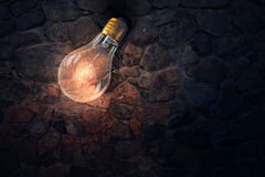 Glowing bulb on brick surface  . Mixed media Royalty Free Stock Images