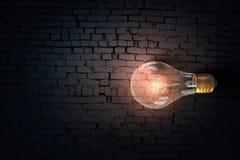 Glowing bulb on brick surface  . Mixed media Stock Image