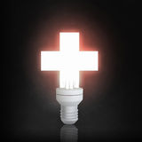 Glowing bulb in darkness. Cross light bulb glowing on dark background Stock Image