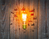 Glowing bulb with drawing graph on the wood Royalty Free Stock Image