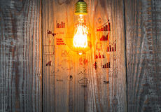 Glowing bulb with drawing graph on the wood Stock Photos