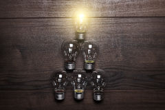 Glowing bulb leadership concept on wooden Royalty Free Stock Photography