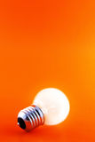 Glowing Bulb on Red. Glowing light bulb on a red background with copyspace Royalty Free Stock Photography