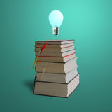 Glowing bulb on top of stack books, green background Royalty Free Stock Images