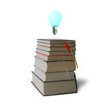 Glowing bulb on top of stack books Royalty Free Stock Images