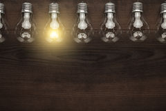 Glowing bulb uniqueness concept with copy space. On brown wooden table Royalty Free Stock Photo