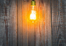 Glowing bulb on the wood Stock Photos