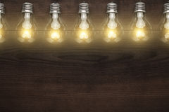 Glowing bulbs over wooden background Stock Photography