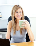 Glowing businesswoman with a cup using her laptop Stock Photo