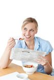 Glowing businesswoman having breakfast and reading Royalty Free Stock Images