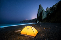 Glowing camping tent on a beautiful sea shore with rocks at night under a starry sky Stock Photos