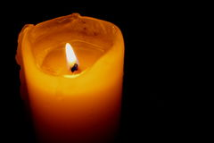 Glowing Candle Against a Black Background Stock Photography