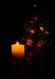 Glowing candle illuminating Christmas tree. Low key. Glowing festive candle illuminating a Christmas tree and decorations. With a black background. Low light Stock Photo