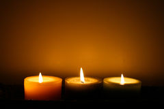 Glowing Candles. Three soft glowing candles with orange background Stock Photo