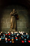 Glowing candles in front of a church statue Stock Photos