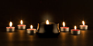 Glowing candles. Group of smaller glowing candles with a bigger burning candle in front on black background Stock Photos