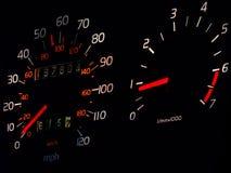 Glowing car spedometer, tachometer in darkness. Glowing car spedometer and tachometer with white miles per hour and orange kilometers per hour markings, against Stock Images