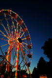 Glowing Carnival Ferris Wheel. A Glowing Carnival Ferris Wheel shot at Dusk Royalty Free Stock Photos