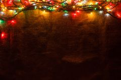 A glowing Christmas garland in the background of burlap in the dark. stock image