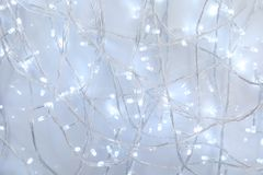 Glowing Christmas garland on light background stock photo
