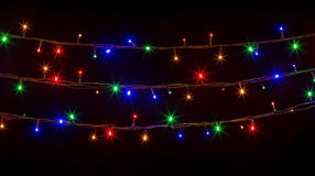 Glowing Christmas lights on black background Royalty Free Stock Images