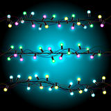 Glowing Christmas lights. Christmas bulb lights on dark blue background. Multicolor lamps and wire silhouette. Celebration Holiday garland Stock Photo