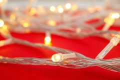 Glowing Christmas lights on color background. Closeup Royalty Free Stock Photos