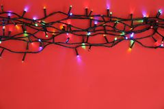 Glowing Christmas lights on color background. Top view Royalty Free Stock Photo
