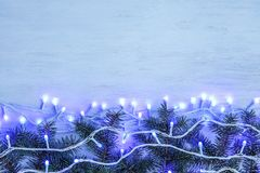 Glowing Christmas lights and fir branches on wooden background royalty free stock photos